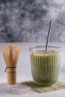 Matcha latte com espuma de creme em copos, tusaku de bambu e matcha em pó na mesa de madeira.