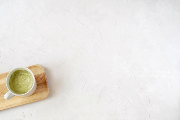 Matcha latte em copo branco na bandeja de madeira