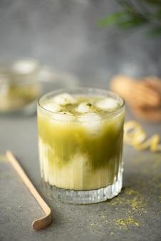 Matcha verde gelado com suco de limão em um copo sobre uma mesa cinza