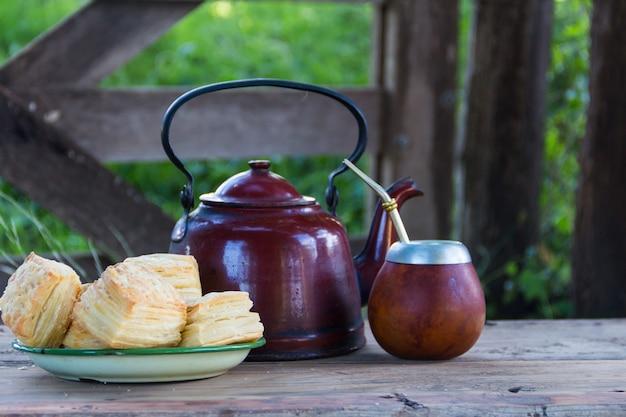 Mate e chaleira com prato de biscoitos argentinos salgados e infusão de erva-mate