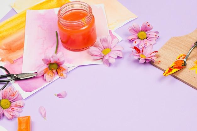 Materiais de arte, flores roxas e óculos na mesa violeta