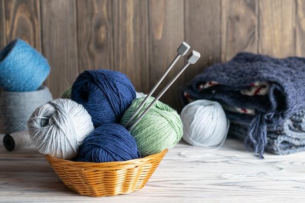 Materiais de confecção de malhas. fio azul e verde em uma cesta com agulhas na madeira