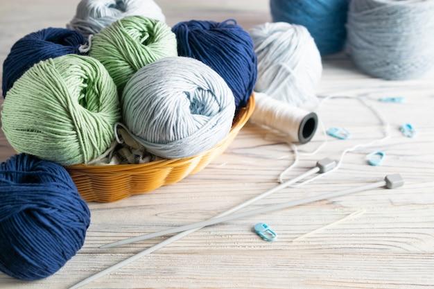 Materiais de confecção de malhas. fio azul e verde em uma cesta com agulhas na mesa de madeira branca