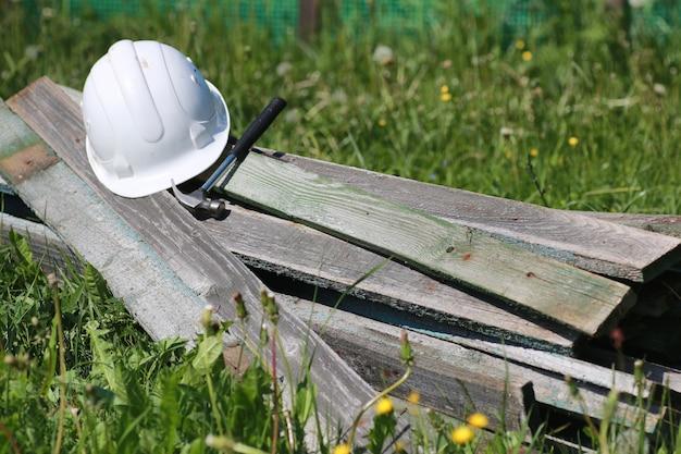 Materiais de construção repousam sobre o martelo de grama e o capacete