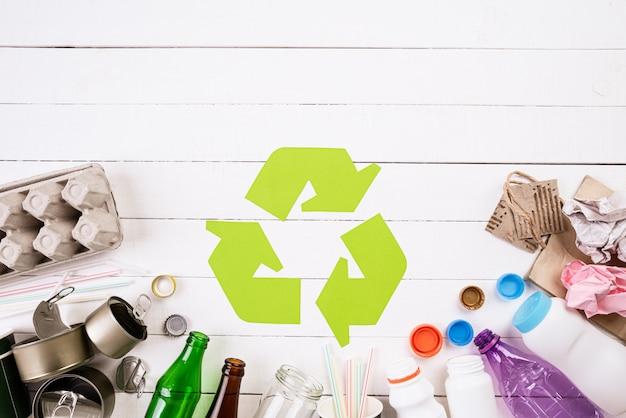 Materiais de lixo diferentes com símbolo de reciclagem.
