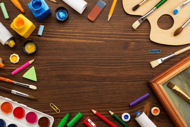 Materiais de pintura e pincéis na mesa de madeira