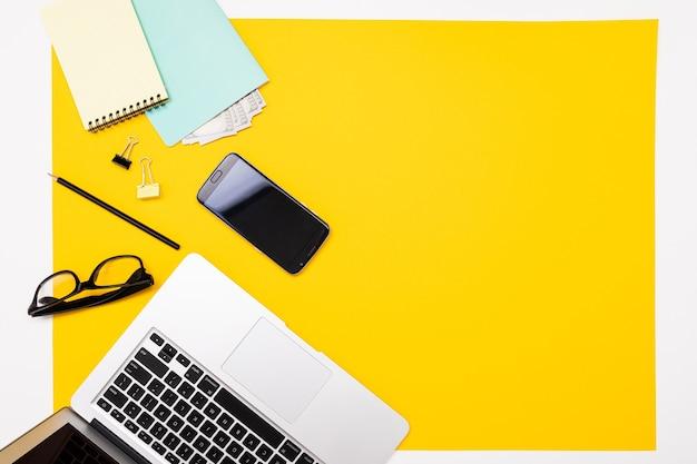 Materiais escolares e de escritório, como bilhetes, canetas, lápis e outros, estão perfeitamente dispostos sobre um fundo amarelo