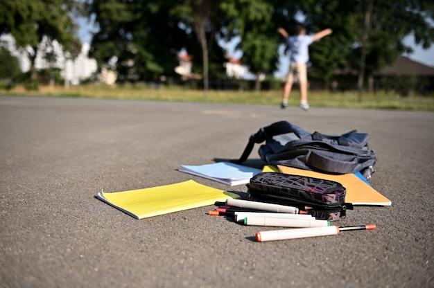 Materiais escolares espalhados e livros de exercícios caindo de uma mochila aberta no asfalto do pátio da escola contra o fundo de um estudante feliz e desfocado levantando as mãos