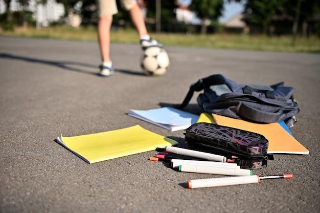 Materiais escolares espalhados e livros de exercícios caindo de uma mochila aberta no asfalto do pátio da escola contra o fundo dos pés de um menino em uma bola de futebol.