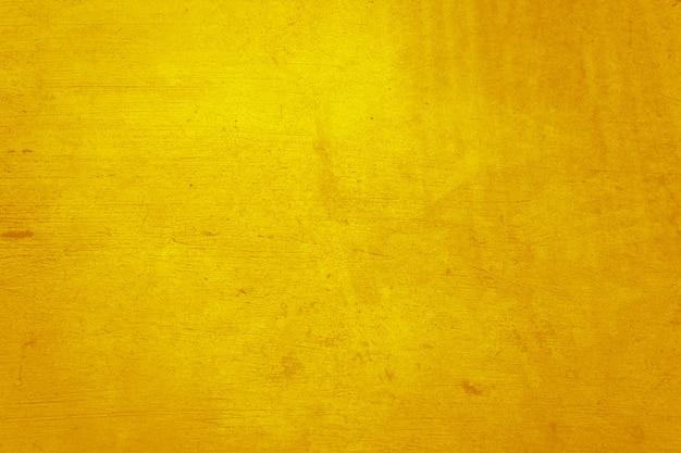 Material amarelo do concreto ou cimento na textura abstrata da parede.