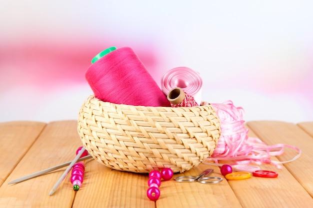 Material de artesanato em uma cesta na mesa de madeira em branco desfocado