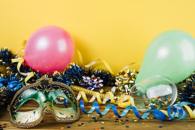 Material de decoração de festa com máscara de penas de carnaval de máscaras e balões na mesa de madeira