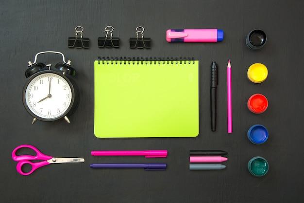 Material de escola colorido, caderno verde e despertador no quadro preto.