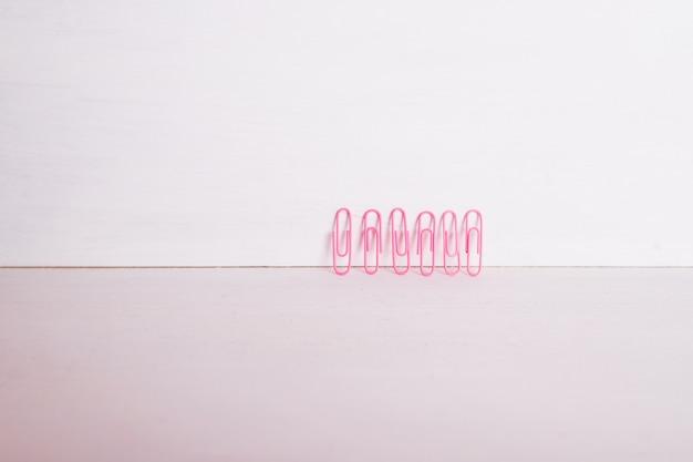 Material de escritório. a linha de composição de clipes de papel multicoloridos em pnk, parede pastel. clipes de papel coloridos. composição criativa. conceito de minimalismo. material de artes e ofícios