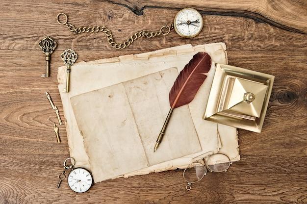 Material de escritório antigo e acessórios na mesa de madeira. papel usado vintage com caneta de pena
