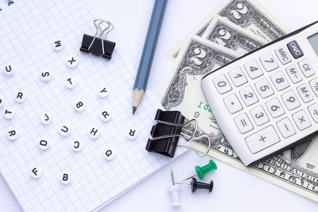 Material de escritório, bloco de notas e dinheiro em um fundo branco