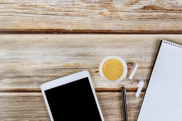 Material de escritório, bloco de notas em espiral em uma mesa com xícara de café tablet digital fones de ouvido sem fio