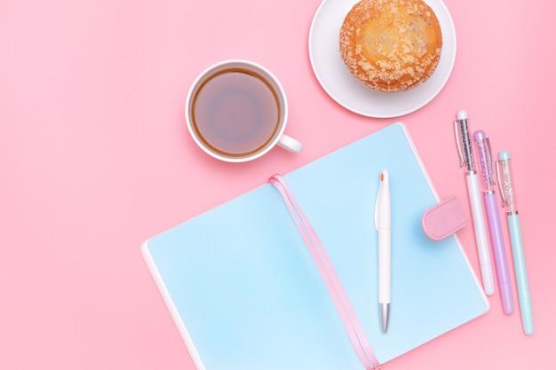Material de escritório de mesa de trabalho, chá quente e bolo em fundo rosa pastel