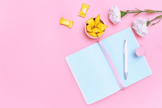 Material de escritório de mesa de trabalho, doces e flor branca em fundo rosa pastel