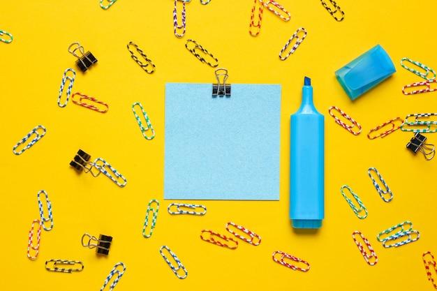 Material de escritório de papelaria. clipe de papel, caneta hidrográfica, pedaço de papel de memorando em fundo amarelo