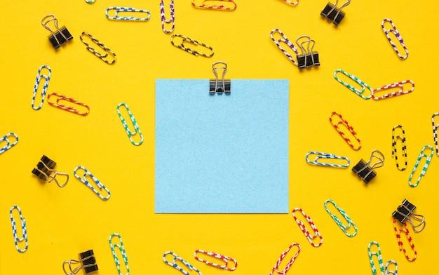 Material de escritório de papelaria. papel de memorando azul, clipe de papel em fundo amarelo.