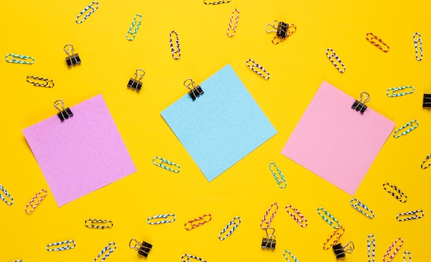 Material de escritório de papelaria. papel de memorando colorido, clipe de papel em fundo amarelo.