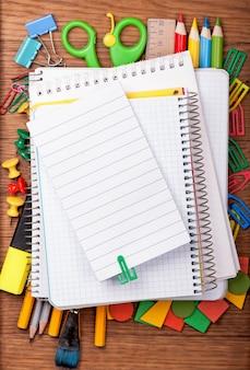 Material de escritório e bloco de notas em branco na mesa de madeira