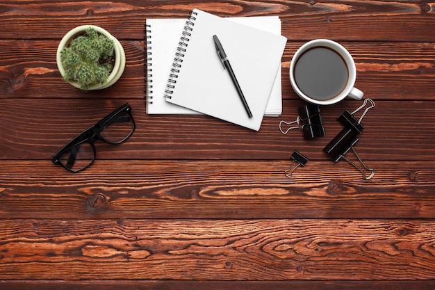 Material de escritório e equipamentos na mesa de madeira escura