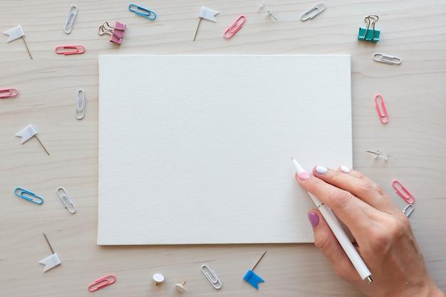 Material de escritório escolar em fundo de madeira. de volta ao conceito de escola. quadro branco com as mãos para espaço de cópia. vista superior pronta para seu projeto.