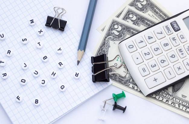 Material de escritório, notebook e dinheiro em fundo branco, close-up