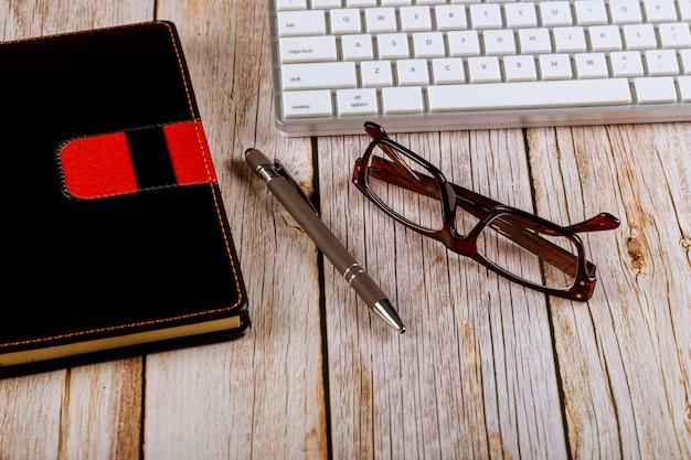 Material de escritório, óculos e bloco de notas preto no teclado do computador ver os de cima na mesa de madeira