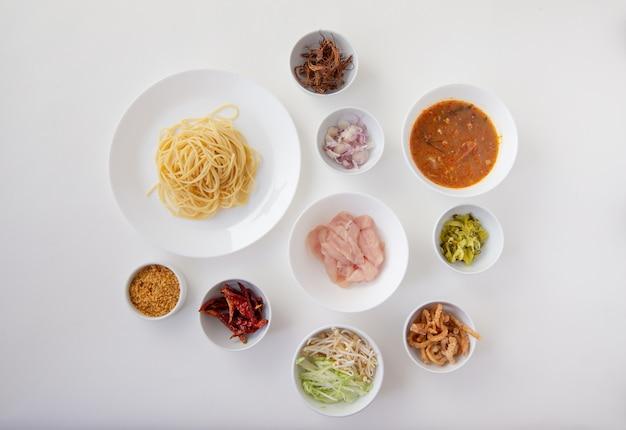 Material de espaguete picante com macarrão de arroz tailandês com molho de frango picante isolado branco