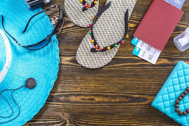 Material de férias de viagem: chapéu, óculos de sol, flip-flops, passaporte e passagens aéreas em fundo de madeira velha