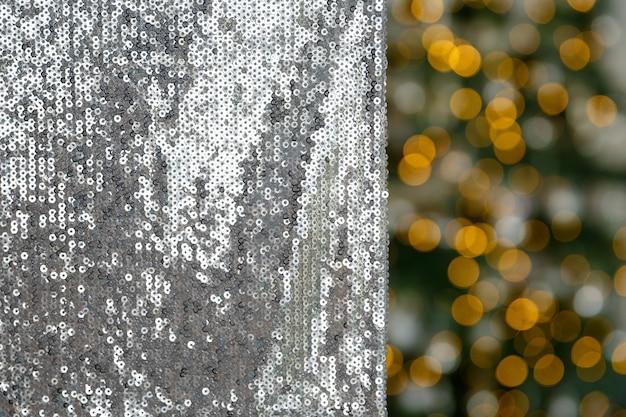 Material de fundo de natal e ano novo bordado com lantejoulas no fundo de luzes de guirlanda
