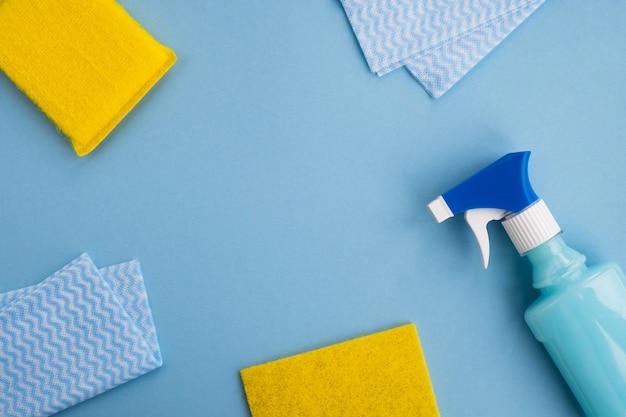 Material de limpeza e esponjas sobre fundo azul claro. limpeza de primavera