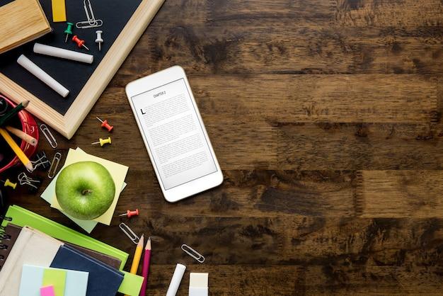 Material de papelaria e educação incliding leitor de livro eletrônico em fundo de madeira