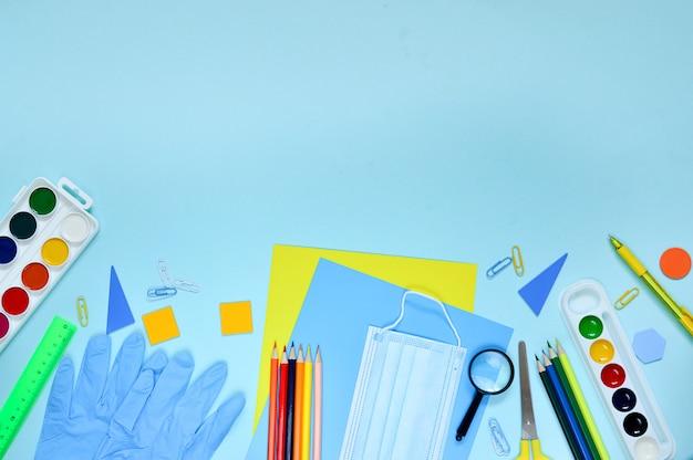 Material de papelaria escolar, máscaras médicas e luvas de proteção médicas em um fundo azul. de volta às aulas após o coronavírus covid-19.