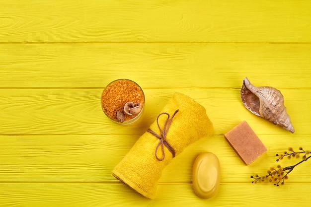 Material de tratamento de spa plana leigos na mesa de madeira amarela. toalha enrolada com sabão e sal.