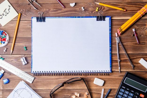 Material do aluno com o caderno de texto na mesa de madeira.