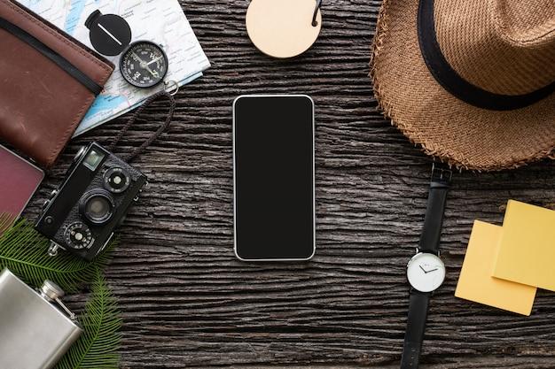 Material do móvel e do explorador da vista superior que viaja com artigo na mesa de madeira velha.