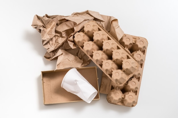 Material ecológico. resíduos biodegradáveis. caixas de papel e copo dispostos em superfície branca.