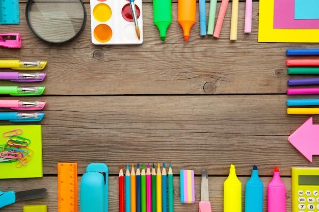 Material escolar, acessórios de papelaria com espaço de cópia no fundo cinza de madeira. vista plana, vista superior