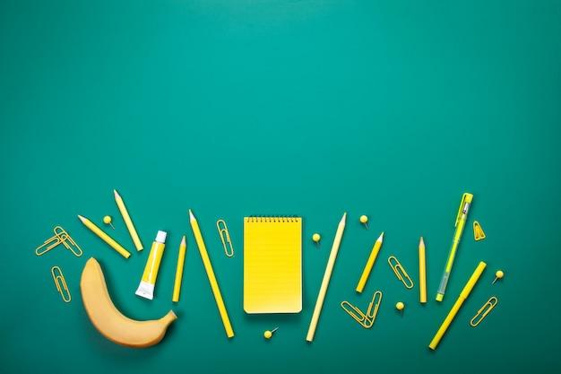 Material escolar amarelo sobre a placa verde. educação, estudar e voltar ao conceito de escola