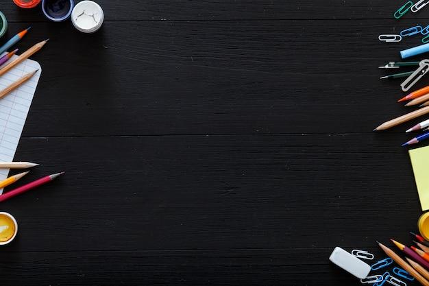 Material escolar, artigos de papelaria, lápis de cor, tintas, papel na mesa de madeira preta escura, volta ao conceito de plano de fundo da escola com espaço de cópia gratuita para texto, ensino fundamental moderno, vista superior