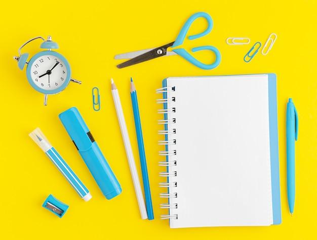 Material escolar azul sobre fundo amarelo com maquete de caderno branco. vista plana, vista superior