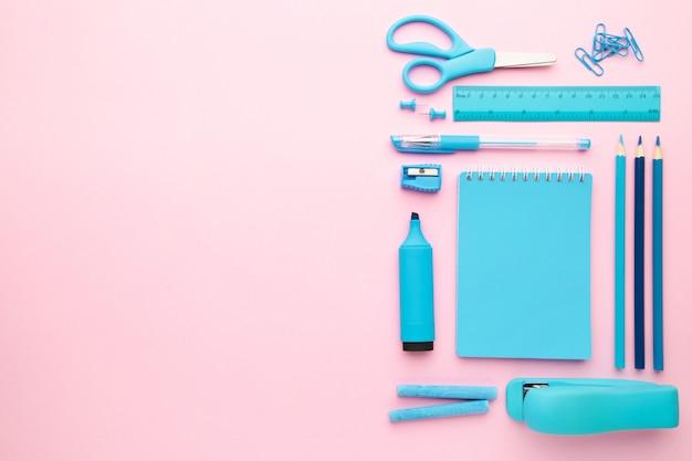 Material escolar azul sobre fundo rosa com espaço de cópia. de volta à escola. postura plana.