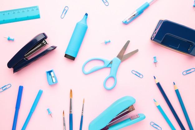 Material escolar azul sobre fundo rosa. de volta à escola. postura plana.