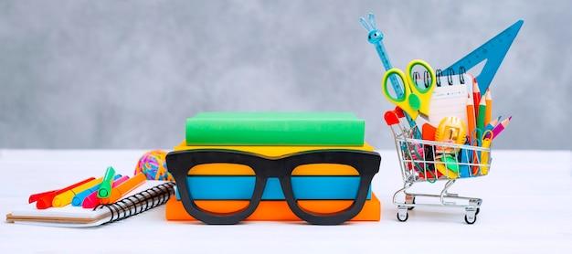Material escolar colorido cesta de compras fundo cinza com um espaço de texto de cópia uma pilha de livros com ...