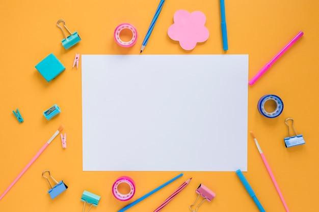 Material escolar colorido com papel em branco no centro