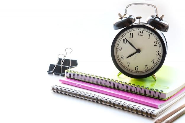 Material escolar colorido, livro e despertador em branco. fechar-se. de volta à escola.